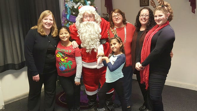 Santa Claus was joined by Santa's Little Helpers (from left) Amy Panichelli,  Hannah Panichelli, Linda Mercogliano,  Adrianna Mercogliano,  Chrissy Iacovelli and Abby Mercogliano to make Christmas a little merrier for some local children in need. Madison Panichelli, Cindy and Connor Hunt and Alex Kaganzev, who also assisted with the effort, are not pictured.