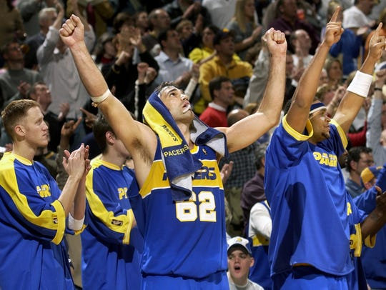 Pacers' Scot Pollard (center, #62) raises his arms