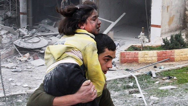 A Syrian man carries his sister who was wounded after a government airstrike hit the neighborhood of Ansari in Aleppo, Syria, on Feb. 3, 2013.
