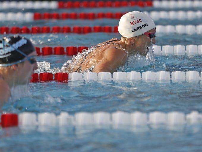 Breeja Larson (white cap) swims the 200 meter breaststroke