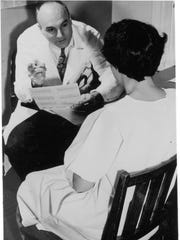 Dr. Thomas Royale Dawber,  one of the early leaders of the Framingham Heart Study, is shown with a program participant.