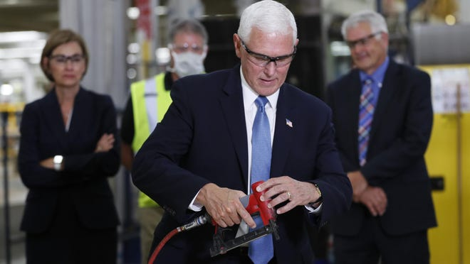 Vice President Mike Pence nails flooring on an RV Tuesday as he tours Winnebago Industries in Forest City.