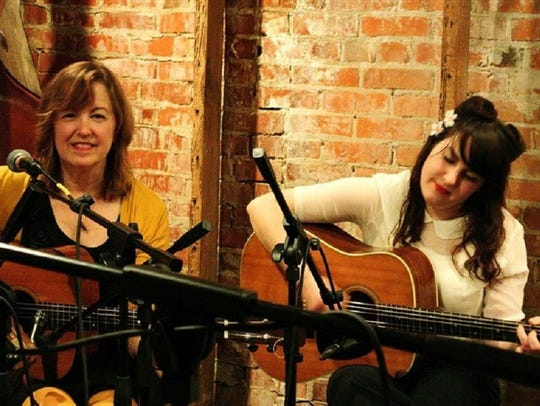 Jane Vidrine, left, plays guitar with her daughter