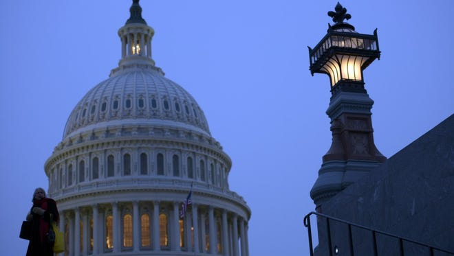 A woman bundled against the cold walks past the U.S. Capitol dome in Washington, D.C.