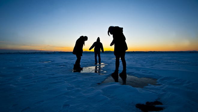 From left, UVM students Monica Johnson of Stamford, Conn., Sam Cohen, of Princeton NJ, and Chloe Bates of Connecticut walk along the ice over Burlington harbor on their way to the breakwater to look out over a completely frozen over Lake Champlain Monday night.