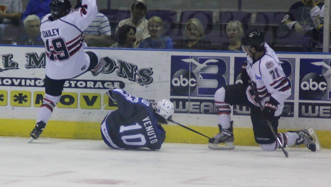 Michael Budd, No. 10, of the Pensacola Ice Flyers, and Huntsville Havoc players Zack Dailey, No. 19, and Frank Schumacher, No. 71, fall to the ice after colliding during the first period of the game Tuesday night at the Pensacola Bay Center.