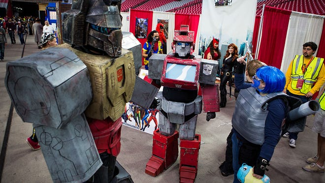 Members of the Arizona Autobots team hang out in front of their booth at Phoenix Comicon Fan Fest on Dec. 12, 2014, in Glendale.
