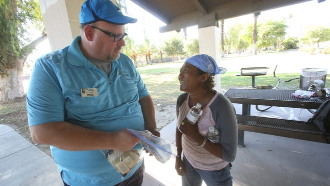 Tom Cox of the Coachella Valley Rescue Mission provides Leslie Bolden with water on a day when heat was expected to reach 120 degrees.