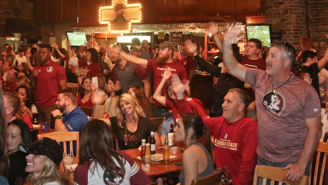 Hundreds of Florida State University and University of Florida football fans watch the annual rivalry game at Seville Quarter Saturday night.  Florida State won 27-2.