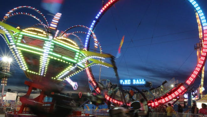 Fairgoers enjoy the numerous rides, games, exhibits, and food vendors during the 81st annual Pensacola Interstate Fair Friday night.
