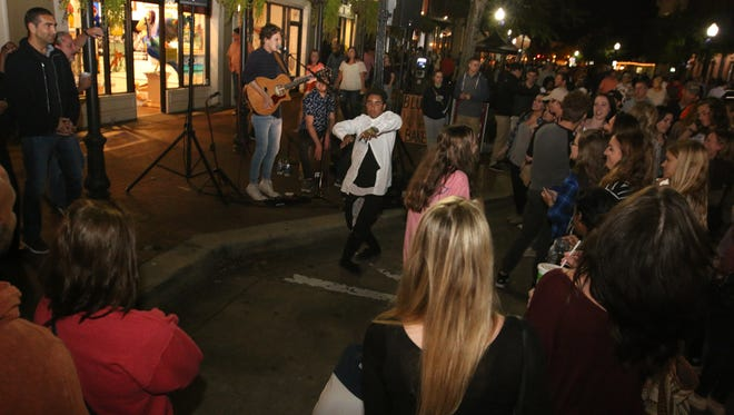 People enjoy April's Gallery Night on Government Street and Palafox Place Friday night.
