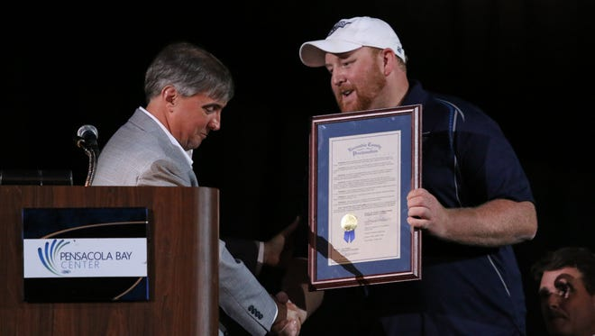 Escambia County Commissioner Grover Robinson IV, left, presents Ice Flyers team owner Greg Harris with a gift during the ceremony celebrating the Ice Flyers as the 2015-2016 SPHL champions at the Pensacola Bay Center on Monday.
