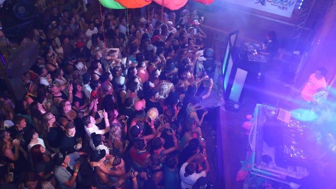 People party at Capt'n Fun Beach Club during a DJ set.