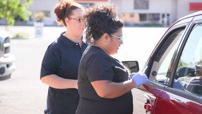 From left, are Kristi Apodaca and Josephine Chavez, HMS employees, who helped during the Free Flu Vaccination Drive Thru Clinc in Silver City.