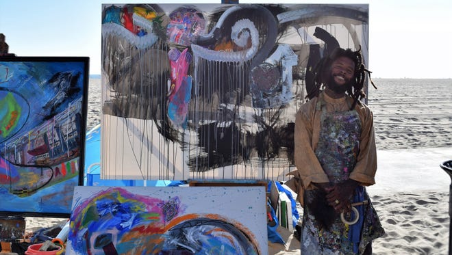 Lee, 28, is part of the homeless population at Venice Beach. He stands near some of his art work.