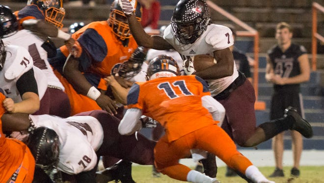 Navarre running back Michael Carter (7) powers his way through the Escambia defensive line behind his blockers during the Region 1-6A quarterfinal game Friday night at Escambia High School.