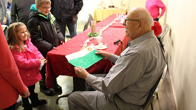 Brooklyn Kuhn, 5, gives a drawing to Lloyd Daiber during his birthday party Sunday, Dec. 18, 2016. Daiber's daughter, Marsha Shumaker, babysits Brooklyn, and they often visit Daiber ,who turned 90 Sunday.