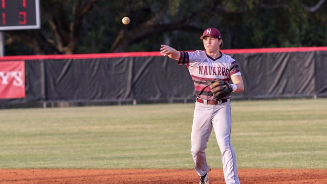 Navarre second baseman Cade Taylor (10) throws the ball to first base to get the Jaguars' Brandon Bergosh out Thursday afternoon.