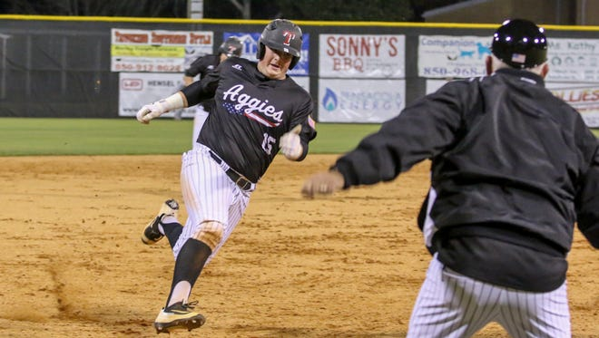 Tate's Logan McGuffey (15) is waved home and scores on a two run triple hit by Hunter NeSmith against Coweta during the 2017 Aggie Classic Tuesday night at Tate High School.