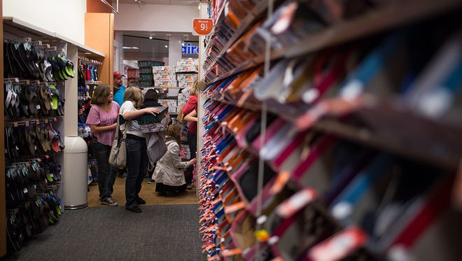 File photo taken in 2014 shows shoppers at a Payless ShoeSource store in Arizona's Superstition Springs Center.