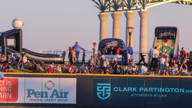 Fans play on new inflatables in the Blue Wahoos Stadium berm Saturday night.