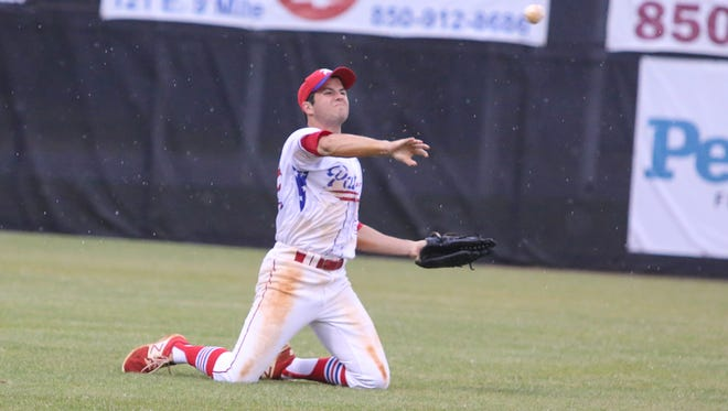 Pace's Bennett Shell (22) slides in to get the ball and throws the ball back in from left field during a rainy District 1-7A semifinal game against Pine Forest at Tate High School on Wednesday, May 3, 2017.
