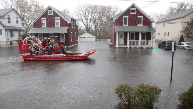Rescue workers enter the flood zone in Moonachie to help residents get to safety after Superstorm Sandy in 2012.