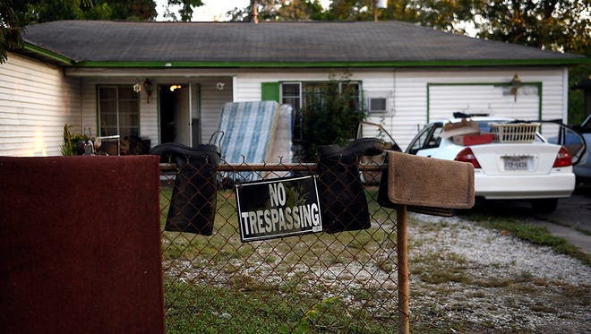A pair of rain boots hangs to dry with carpets and other household items in front of Jonathan Bates' home in East Houston  on Thursday.