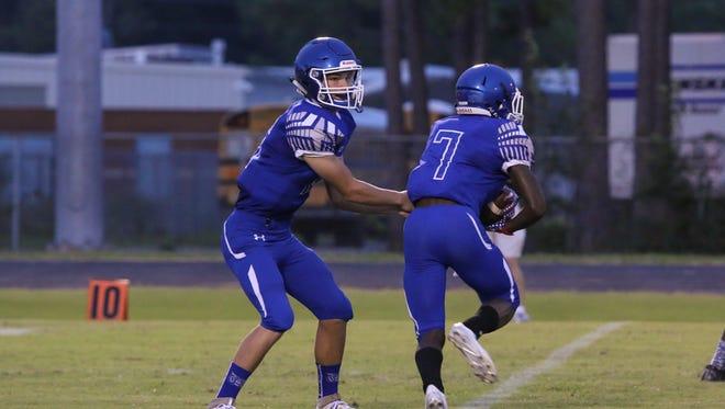 Washington quarterback Joe Slattery (16) hands off to Julian Robinson (7) against the Navarre Raiders at Washington High School on Friday, Sept. 1, 2017.