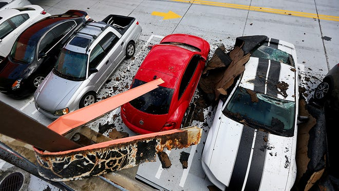 Several cars on the roof of the City of Palms Garage in downtown Fort Myers were damaged by Hurricane Irma. Pieces of metal, pictured, were wrapped around several garage polls.