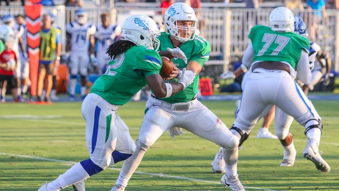 UWF quarterback Mike Beaudry (13) hands the ball off to Jacari Footman (22) in first home game of the 2017 season at Blue Wahoos Stadium on Saturday, Sept. 16, 2017.