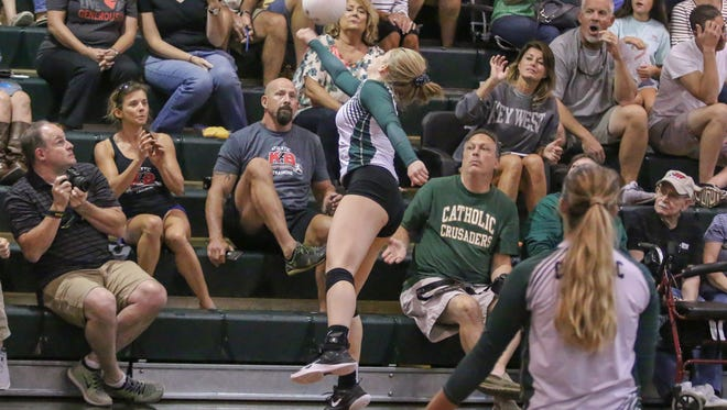 Catholic's Ellen Floyd (2) reaches into the crowd to return the ball hit by Niceville at Catholic High School on Wednesday, Sept. 20 2017. Niceville beat Catholic in three straight sets.