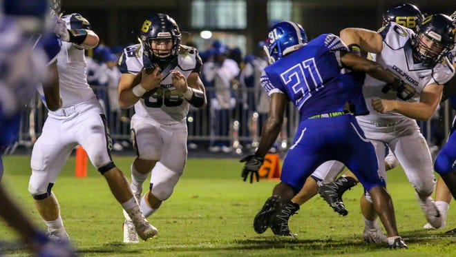 Gulf Breeze running back Tyler Dittmer (36) makes his way through the Wildcats' defensive line at Washington High School on Friday, Sept. 22, 2017.