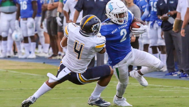UWF wide receiver Rodney Coates (2) tries to get away from Mississippi College's Blake Miller (4) at Blue Wahoos Stadium on Friday, Oct. 6, 2017.  The game originally was scheduled for Saturday, but was moved up a day due to concerns about the forecast of Tropical Storm Nate.
