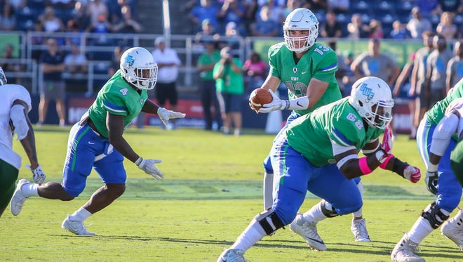 UWF's Leroy Wilson (4) takes the handoff from quarterback Mike Beaudry (13) and runs for a touchdown against Delta State at Blue Wahoos Stadium on Saturday, October 14, 2017.
