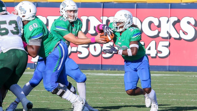 UWF's Anthony Johnson, Jr. (32), a Pace High School graduate, takes the handoff from quarterback Mike Beaudry (13) against Delta State at Blue Wahoos Stadium on Saturday, October 14, 2017.