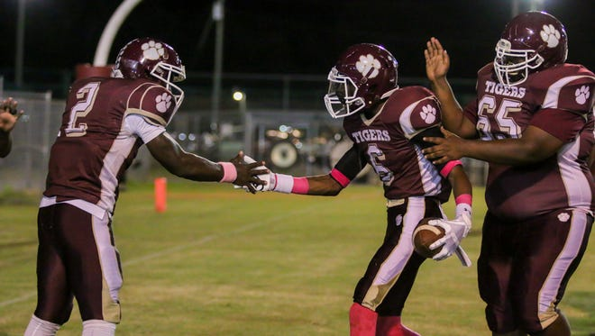 Tyrese Albritton (2) and Terinn Tanksley (65) congratulate Antarus Jackson (6) after he scored a PHS touchdown against district rival Mosley at Pensacola High School on Friday, October 20, 2017.