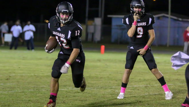 West Florida's Bryant Johnecheck (12) takes the handoff from quarterback Trevor Jordan (9) runs the ball against Pensacola High at Woodham Middle School on October 27, 2017.  West Florida clinched the District 1-5A title after beating PHS 33-0.