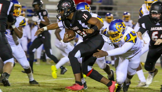 West Florida's Devin Abrams (16) pushes his way through the Tallahassee Rickards defensive line in the Region 1-5A quarterfinal game at Woodham Middle School on Friday, November 10, 2017.