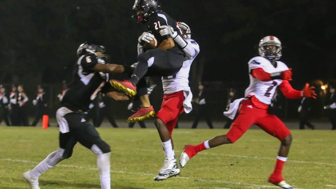 West Florida's Amir McDaniel (21) makes a leaping interception against Wakulla during the Region 1-5A semifinal game at Woodham Middle School on Friday, November 17, 2017.