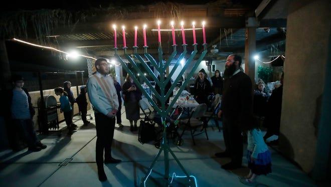 At far right, Rabbi Benny Lew and Rabbi Dovid Tsikman light the Menoraon the last night of Hanukkah at the Chabad of Rancho Mirage, The Torah Oasis.