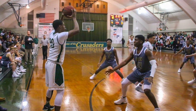 Catholic's Kyheem Coleman (20) looks for an open teammate to pass to against Foley in their quarterfinal game during the 6th annual Crusader Classic at Catholic High School on Wednesday, December 27, 2017. Catholic won 70-48 and will face West Florida in the semifinals on Thursday.