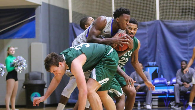 UWF's Darryl Tucker (21) comes down with a pass and collides with Delta State's Mitch Keller (33) at the University of West Florida Field House on Tuesday, January 9, 2018.