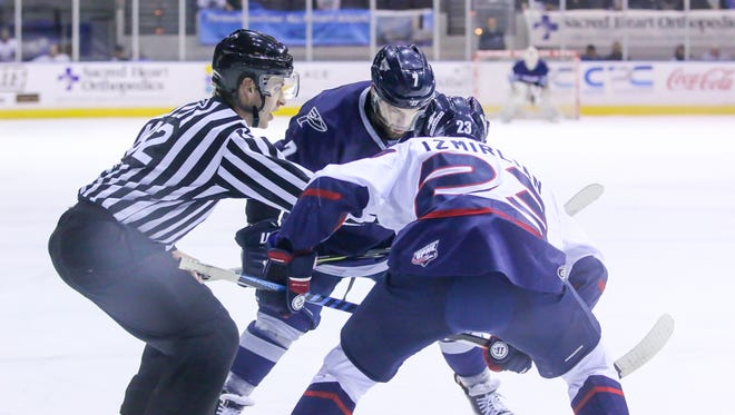 Pensacola's Josh Cousineau (7) takes a faceoff against Macon's Chris Izmirlian (23) at the Pensacola Bay Center on Sunday, January 14, 2018. Though Macon won the game 4-2, the Ice Flyers have won three of their last five games and stay in first place with 43 points.