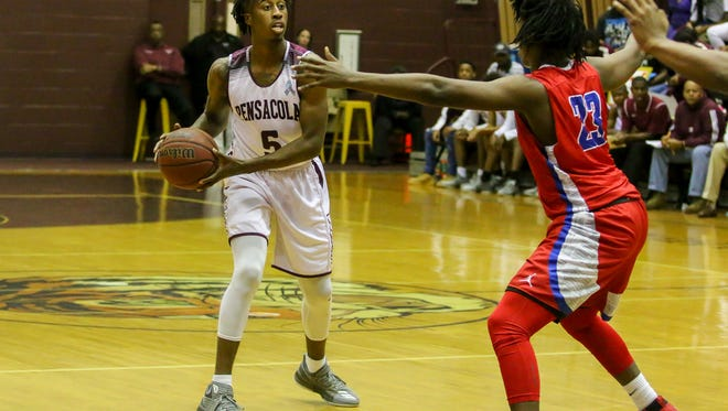 PHS' Shawndarius Cowart (5) looks to pass the ball as Pine Forest's Divincent Madison (23) defends against him at Pensacola High School on Friday, January 19, 2018.  PHS won 64-59.