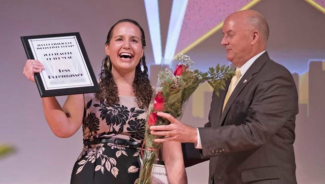 Tess Borengasser receives her Indian River County teacher-of-the-year award and a bouquet from Superintendent Mark Rendell.