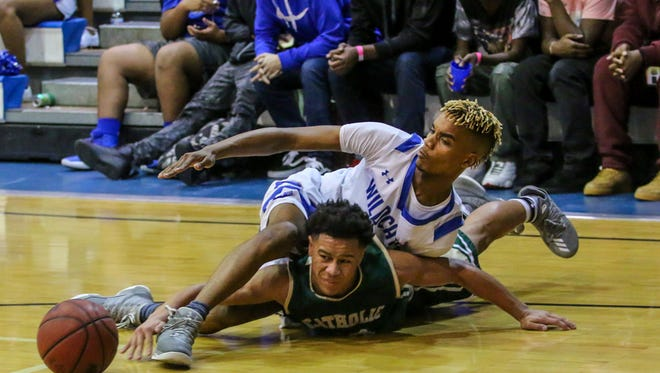 Catholic's Demarius Nickerson (10) and Washington's Michael Randolph (5) end up on the court after fighting for the ball at Washington High School on Friday, January 26, 2018.