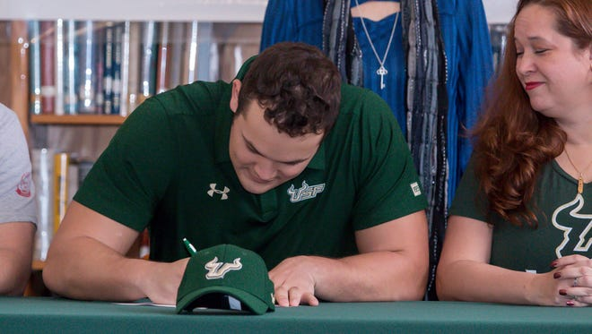 Catholic High School offensive lineman Ethan Watson signs a letter of intent to play football at the University of South Florida as his mom, Kelli, watches on Wednesday, Feb. 7, 2018.