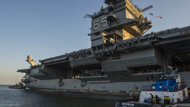 The retired aircraft carrier USS Enterprise is moved by tugboats away from the pier at Naval Station Norfolk in Virginia.
