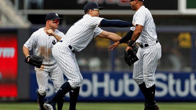 New York Yankees left fielder Giancarlo Stanton (27) celebrates with New York Yankees center fielder Aaron Hicks (31) in front of New York Yankees left fielder Brett Gardner (11) after defeating the Cleveland Indians at Yankee Stadium.